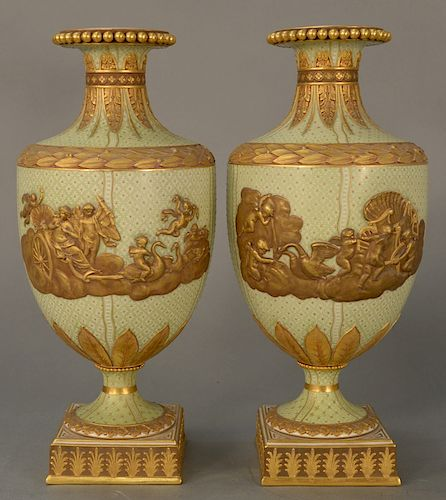 Pair of Wedgwood gilt decorated Victoria ware vases/urns,  pale green with gold jeweled ground, central gilt relief chariot with put...