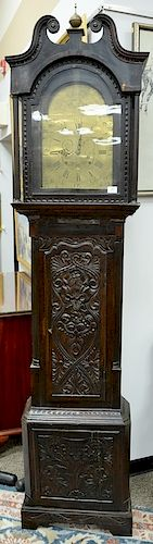English oak tall clock with carved door and base,  having brass works with brass dial marked: Stratford on Avon, Warwickshire, insid...