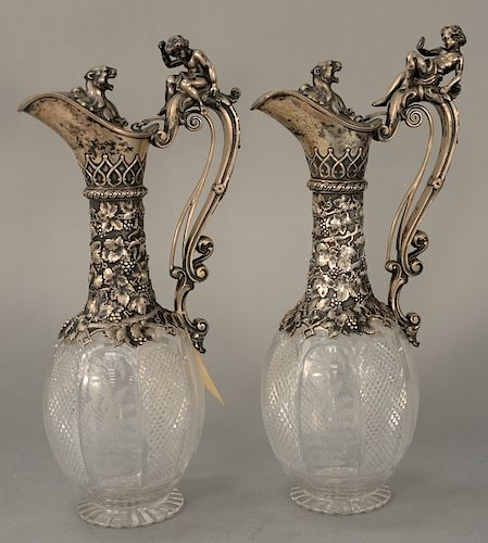 Pair of figural Claret Jugs,  silver tops over crystal body, handles mounted with putti fearing lion and lunging lion, pull handle...