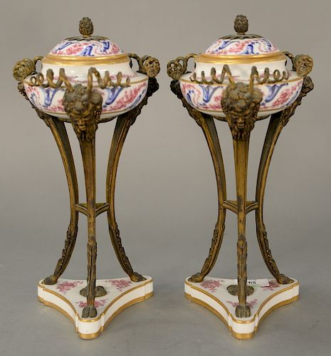 Pair of Sevres covered urns mounted in bronze supports,  Classical face, legs ending in hoof feet, set on triangular porcelain base ...
