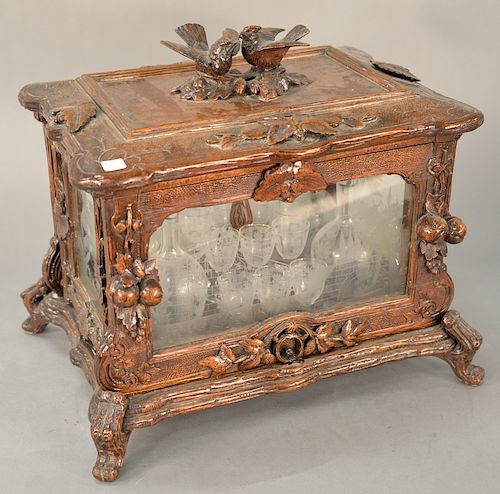 Black forest tantalus,  having rectangular lift-top with two bird finial above hinged glass case with fruit and leaf accents, having...