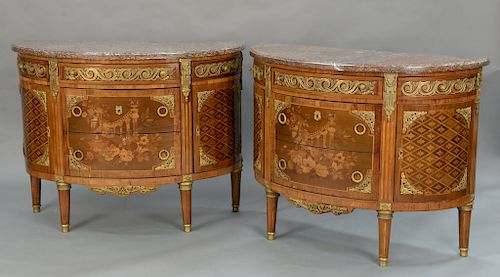 Pair of Louis XVI style demilune commodes with marble tops,  over cabinet of three center drawers, inlaid and gilt bronze mounted fl...
