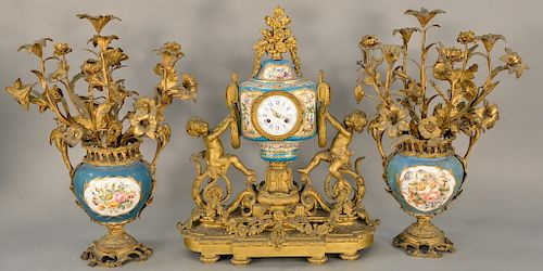 French Raingo Freres gilt bronze and porcelain three piece clock set,  having Serves type body topped with gilt bronze flowers, all ...