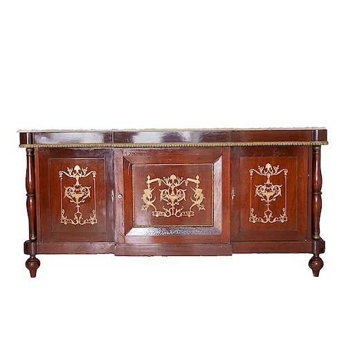 Trinchador. Siglo XX. Elaborado en madera tallada y enchapada. Cubierta irregular de mármol, tres puertas abatibles.