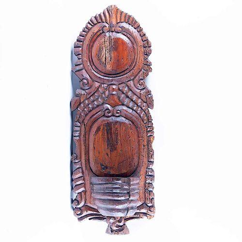 Benditero. México, siglo XX. Talla en madera entintada acabado rústico. Decorado con motivos orgánicos,estriados con depósito inferior.