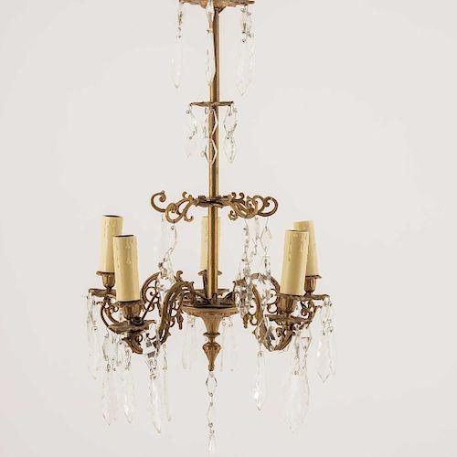 Lámpara de techo. Siglo XX. Elaborada en bronce y cristales facetados.Para 5 luces. Con fuste tubular compuesto,decorada con estriados.