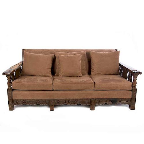 Sofá de tres plazas. Siglo XX. En talla de madera. Con tapicería de tela color marrón. Respaldo cerrado y soportes lisos.