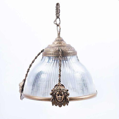 Lámpara de techo. Siglo XX. Estructura de metal dorado, con pantalla de cristal. Para 1 luz. Decorada con mascarones y atorzalados.