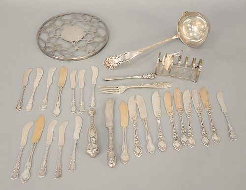 Sterling silver lot including butter knives, toast holder, and large ladle. 25 troy ounces plus a silver overlay plate and two handles.