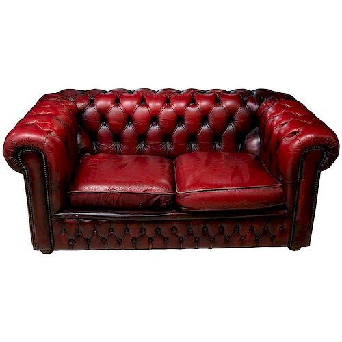 Love seat tipo Chesterfield. Siglo XX. Estructura de madera. Con respaldos y asientos capitonados en piel color vino.