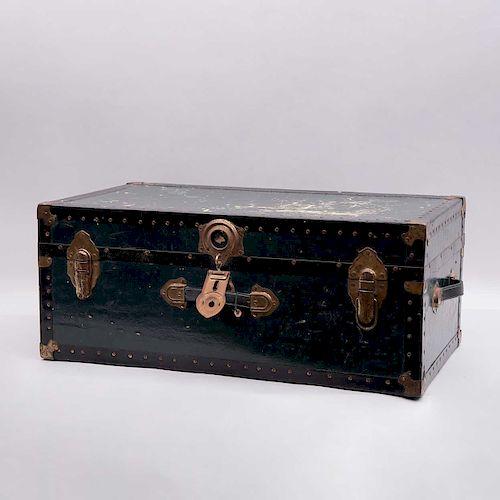 Baúl de viaje. Siglo XX. Estructura de cartón comprimido, con aplicaciones de lámina de metal laqueado y herrajes de metal dorado.