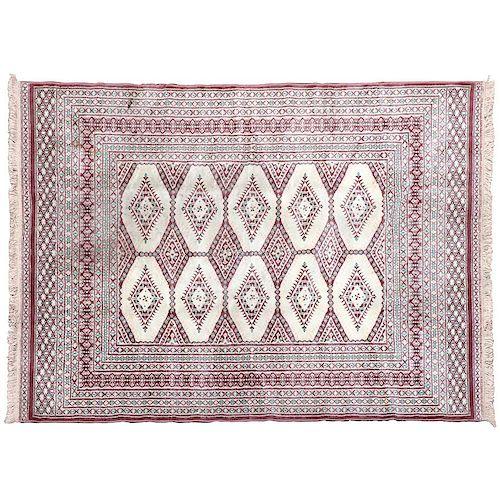 Tapete. Siglo XX. Marca Mashad. Estilo Bokahara. Elaborado en fibras de lana y algodón. Decorado con motivos romboidales y geómetricos.