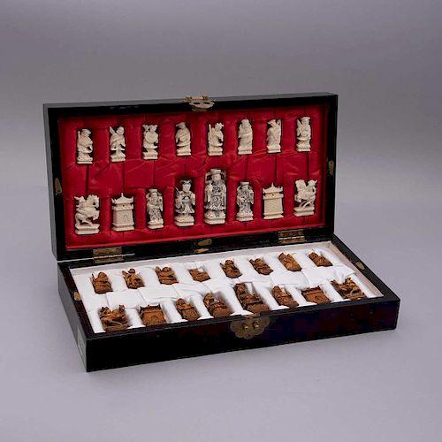 Juego de ajedrez. China, siglo XX. Tallas en marfil con detalles esgrafiados en color negro y laqueado. Con tablero. Piezas: 33