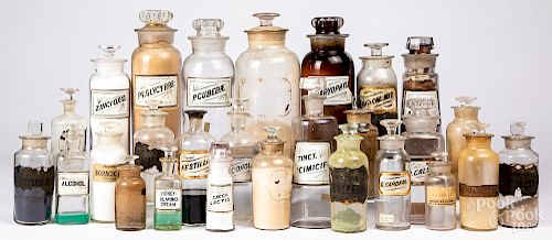 Group of colorless labeled apothecary bottles