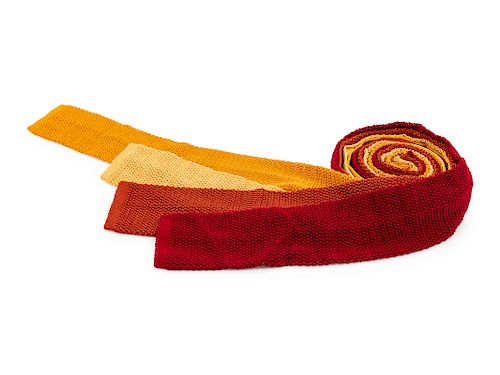 Four Hermes knit ties, one yellow, one red, one orange, one burnt orange.