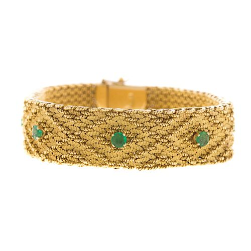 A Ladies Wide 18K Woven Bracelet with Emeralds