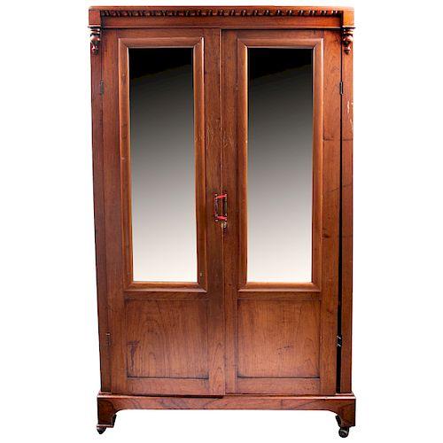 Ropero. Siglo XX. Elaborado en madera tallada. Con 2 puertas abatibles con lunas rectangulares biseladas y soportes con ruedas.