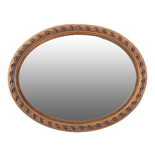 Espejo. SXX. Elaborado en resina. Con luna oval biselada. Decorado con esmalte dorado, elementos vegetales y lacería. 70 x 89 x 6 cm.