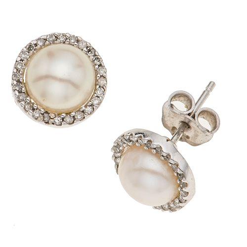 Par de broqueles con perlas y diamantes en oro blanco de 14k. 2 perlas cultivadas color blanco de 7 mm. 42 diamantes corte 8 x 8.