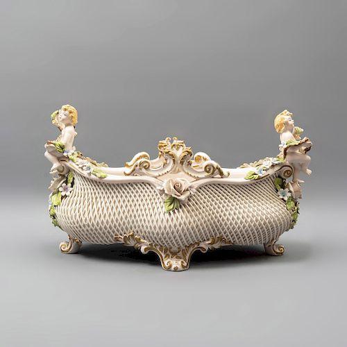 Centro de mesa. Italia. Siglo XX. Elaborado en porcelana Capodimonte. Decorado con cestería, par de niños, etc. 23 x 39 x 22 cm.
