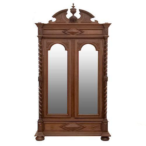 Armario. Francia. SXX. En madera de nogal. Con 2 puertas abatibles con espejos de lunas biseladas y cajón. 290 x 162 x 59 cm.