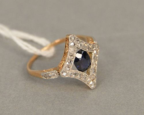 14 karat gold and platinum filligree ring set with cusion cut blue sapphire surrounded by diamonds, approximately 5.2mm x 6.4mm. size 5 3/4.
