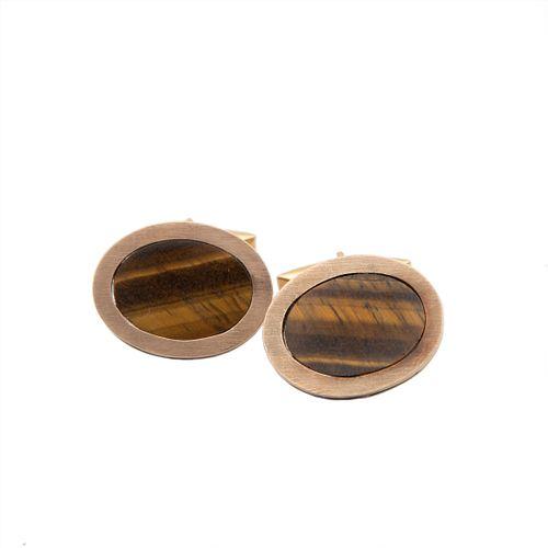 Par de mancuernillas con ojo de tigre en oro amarillo 12k. 2 mosaicos de ojo de tigre corte oval. Peso: 13.3 g.