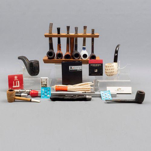 Lote de 23 piezas. Diferentes orígenes, diseños y materiales. SXX. Consta de: 2 boquillas, 5 encendedores, 9 pipas, otros.