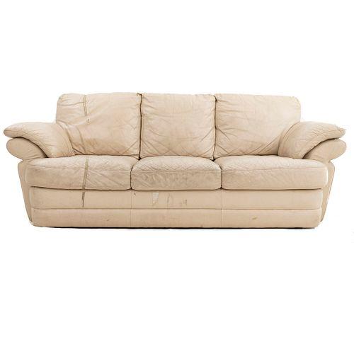 Sofá de 3 plazas. Siglo XX. En talla de madera. En polipiel color beige. Con respaldo cerrado y asientos con cojines.