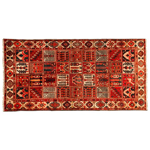 Tapete. Persia, siglo XX. Diseño Casetonado. Anudado a mano con fibras de lana y algodón. 310 x 156 cm.