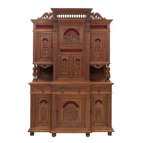 Buffet. Francia. Siglo XX. Estilo Bretón. En talla de madera de nogal. A 2 cuerpos. Con 3 cajones y 6 puertas. 240 x 160 x 52 cm.
