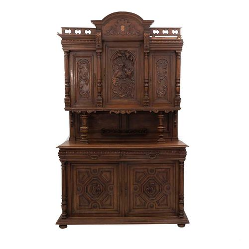 Buffet. Francia. Siglo XX. Estilo Enrique II. En talla de madera de nogal. A 2 cuerpos. 2 cajones con tiradores de metal dorado