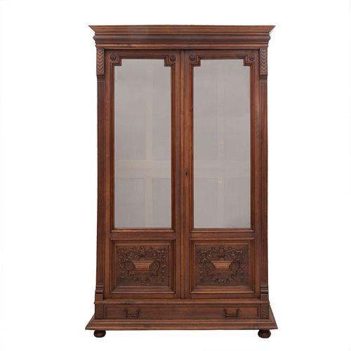 Librero. Francia. Siglo XX. Estilo Enrique II. En talla de madera de nogal. 2 puertas con cristal, cajón, soportes tipo bollo.