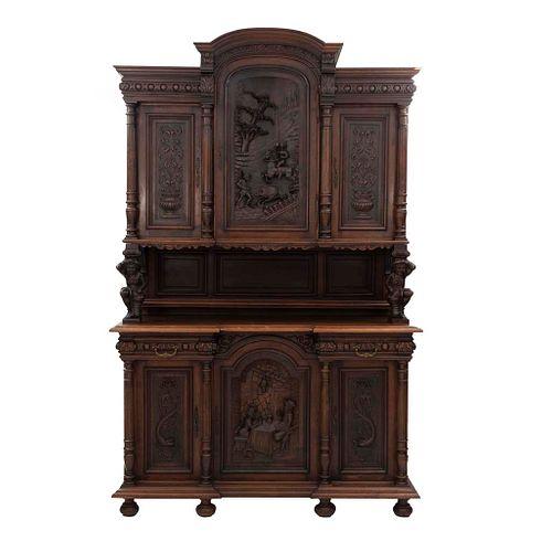 Buffet. Francia. Siglo XX. Estilo Enrique II. En talla de madera de nogal. A 2 cuerpos. 2 cajones con tiradores de metal.