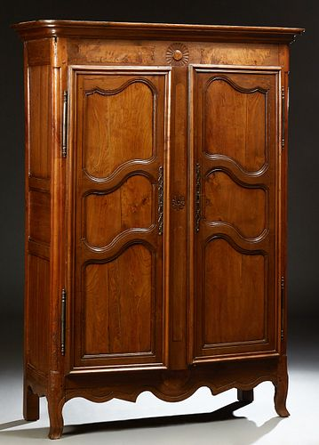 French Provincial Carved Oak Armoire, 19th c., the stepped rounded corner ogee crown over double three panel doors with iron fiche h...