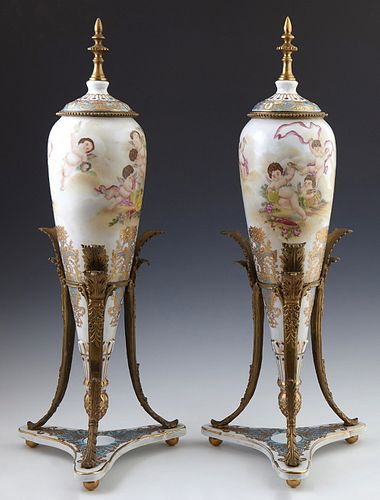 Pair of Sevres Style Bronze Mounted Covered Porcelain Urns, 19th c., of tapering form, with gilt and polychromed frolicking putti de...