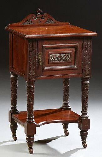 English Carved Mahogany Nightstand, early 20th c., with an arched finialed back on a stepped top, over a cupboard door on twist carve..