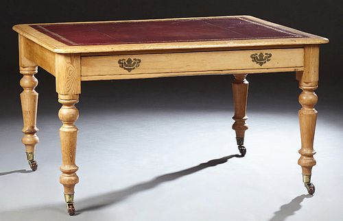 English Carved Pine Writing Table, 19th c., the rounded edge and corner top with an inset gilt tooled leather top, over a long friez...