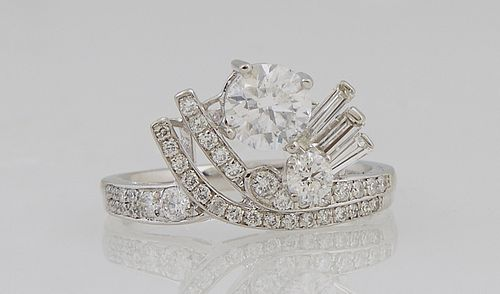 Unusual Platinum Lady's Dinner Ring, with a .82 carat round diamond flanked by two rounded diamond mounted rods left and three bague...