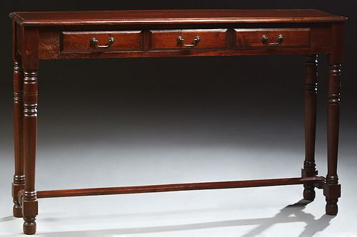 English Victorian Style Carved Mahogany Console Table, 20th c., the stepped rounded edge top over three frieze drawers, on turned ta...