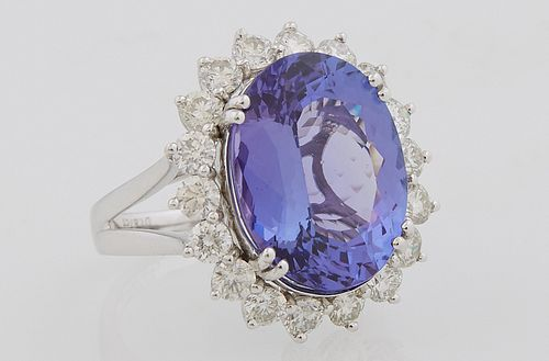 Lady's Platinum Dinner ring, with a 10.78 carat oval tanzanite atop a border of round diamonds, on a split sided band, size 7, with...