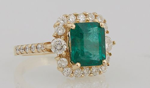 Lady's 14K Yellow Gold Dinner Ring with a 3.1 carat emerald, atop a border of round diamonds, the shoulders of the band also mounted...