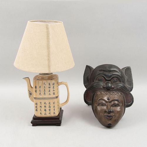 Lote de 2 piezas orientales. Siglo XX. Consta de: Lámpara de mesa. Diseño a manera de tetera y máscara del Sudeste asiático.