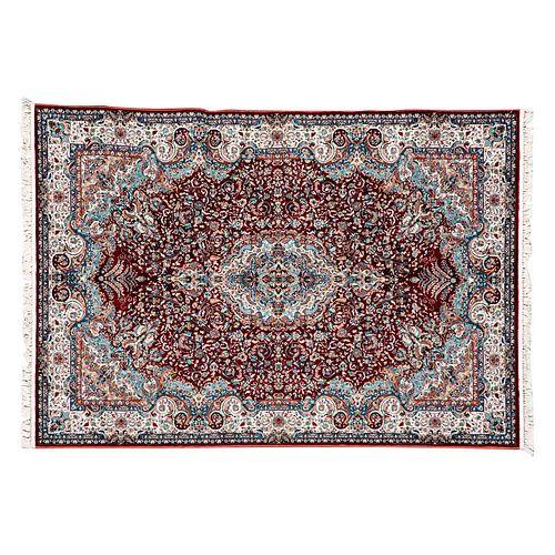 Tapete. Persia, siglo XXI. Estilo Mashad. Elaborado en fibras de lana ensedada. Medallón central sobre fondo rojo, azul y beige.