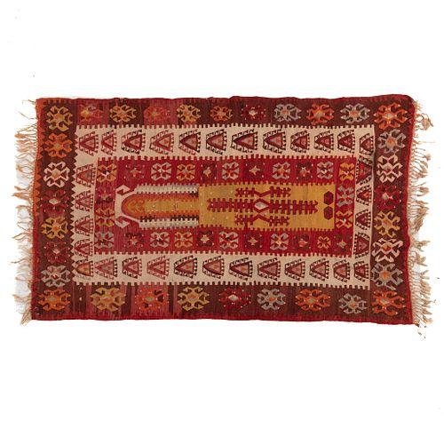 Tapete. Siglo XX. Elaborado en fibras de lana y algodón. Decorado con medallón central y elementos geométricos. 184 x 110 cm.