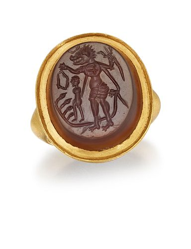 AN INTAGLIO HARDSTONE RING, the dark orange-brown agate slice, carved with