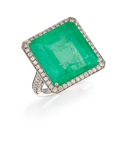 AN EMERALD AND DIAMOND RING, the octagonal step cut emerald, 27.70cts, in a