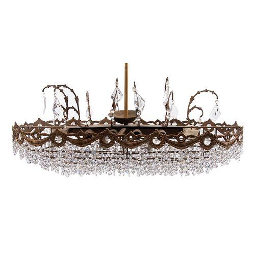 Lámpara de techo. Siglo XX. Diseño oval. Elaborado en metal dorado. Para 9 luces. Decorado cuentas y almendrones facetados de cristal.80 x 40 cm