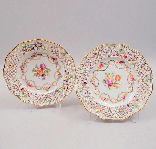 Par de platos decorativos. Alemania. Años 70. Elaborados en porcelana Schumann. Decorados con elementos florales y calados.