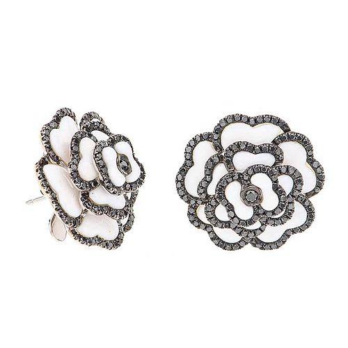 Par de aretes con simulantes y resina en plata paladio. Diseño de flor. Peso: 13.8 g.